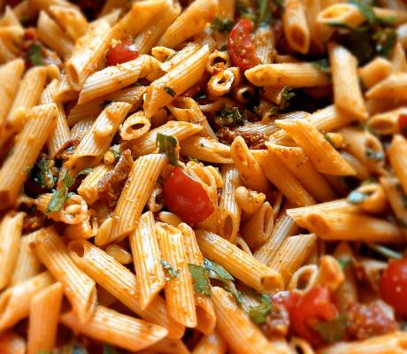Rucola-Nudel-Salat mit Tomatenfilets verfeinert mit frischen Basilikum Pesto und Pinienkernen