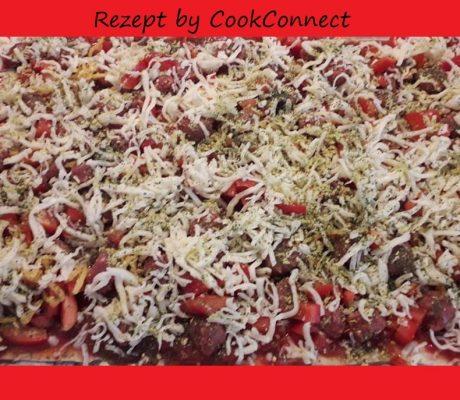 Basilikum Pizza mit französischer Merguezwurst, Pesto und frischen Kräutern