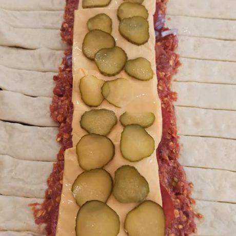 Pizzataschen gefüllt mit Hackfleisch, Zwiebeln, Tomaten, Schmelzkäse und Essiggurken
